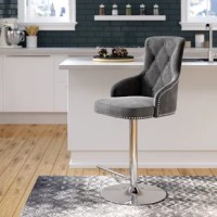 Marrying modern and glamorous elements, this swivel bar stool makes a statement as it offers a spot to sit in any space. Founded atop a metal pedestal base with a slender footrest and a sleek chrome finish, its frame is padded with foam, upholstered with velvet fabric, and dotted with button-tufted details for a textured and inviting look. Nailhead trim surrounds the seat and back for a decorative touch. Thanks to a convenient lever beneath the bucket seat, you can tweak this stool's seat...
