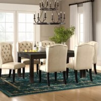 Seat friends and family in style with this seven-piece dining set, the perfect anchor for any traditionally-styled dining space. Each piece in this set – including a table and six chairs – is crafted from solid and manufactured wood awash in an antique black finish. The table stands atop block legs and features a subtle, streamlined silhouette, while each of the wingback-style chairs is wrapped in linen upholstery and accented by a line of nailhead trim.