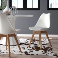 Brimming with streamlined style, this Dakota Upholstered Dining Chair brings a dash of modern flair as provides a spot to sit. Founded atop four splayed wooden legs in a walnut finish, this plastic piece is padded with foam and upholstered with solid-hued faux leather that's easy to clean – just wipe down with a damp cloth! Versatile white hue and low profile contribute to its understated feel, while felt foot pads underneath provide a practical touch to keep your floors scratch-free. After...