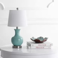 Perfect for adding a touch of style while they light up a room, table lamps are versatile, space-conscious lighting fixtures – and we can't get enough of them! This lamp, for example, is a great option for adding an understated seaside touch to any ensemble: crafted from ceramic, it features a vase-like silhouette with a light blue hue at home in coastal ensembles. Up top, an off-white cotton empire shade helps diffuse the included 4W bulb.