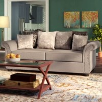 Take-out and TV night just got more exciting with this stylish sofa. Made in the USA, it's built on a solid and engineered wood frame, and upholstered in 100% polyester fabric in a neutral gray hue. This couch has curvy, rolled arms to bring it classic appeal with a glam twist, while its nailhead trim adds eye-catching appeal, giving it an updated look that's ideal for your living room, whether it leans more traditional or French country. Plus, it arrives with six toss pillows that comprise...