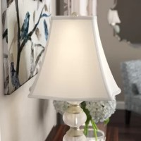 When it comes to mood lighting, lamp shades can make it or break it. They affect the light in our room, which in turn affects the ambience. Find the lighting you love with this lamp shade. Crafted from hand-tailored silk, it boasts neutral tones so as not to offset your existing decor, while also featuring a square bell shape for a touch of tradition. Finished in brass, its metal harp has a spider-fitter attachment, allowing it to cover any compatible bulb up to 150 W.  An off-white softback...