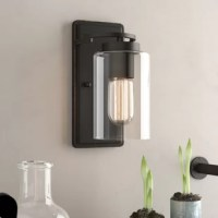 Searching for something special to spruce up the master suite? Switch out your nightstand lamp for this sconce on the wall above! Not only does it lend a fashion-forward feel to your ensemble, but it also frees up space for displaying accents and keeping nighttime essentials on hand. It features a rectangular backplate and curved support finished in a metallic tone. A single light is highlighted by a cylindrical glass shade.