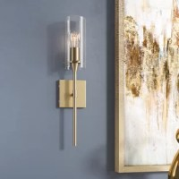 Looking to lighten up a dim room? If you can't sacrifice square footage, a wall sconce is a great option for (literally) brightening bare walls with a pop of decor and illumination. Take this one, for example: perfect for a modern twist on a torch. This piece is crafted from an iron base with a clear glass cylinder shade. A single 60 W bulb lights this piece, although none is included. And since it's designed to be compatible with damp spaces, this piece is a great option for rounding out use...