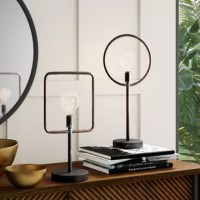 Rustic industrial style meets modern minimalism in this two-piece geometric table lamp set! Crafted of metal in a faux-rusted finish for a weathered, well-worn aesthetic, each lamp features a slender tube post body on a round pedestal base. With one lamp featuring a hoop frame and the other a rounded rectangle, each lamp features an exposed LED Edison bulb (included) to disperse ambient light throughout your space. Powered by AA batteries (not included), each portable lamp is operated by a...