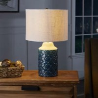 Artisan-inspired craftsmanship define this product, the perfect offering for brilliant light. The large cylindrical base, crafted in ceramic, features a unique scale pattern texture reaching just up to its neck, and is finished with a smooth fired glaze. This sea-inspired lamp is topped with a soft linen drum shade, evoking crisp sails upon a storied maritime vessel.