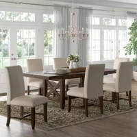 This 7PC Dining Set creates a warm gathering place for the best part of your day. This set includes a table and six fabric side chairs. It features a trestle style table with unique cross panel legs and an 18-inch removable leaf. Distressed markings can also be found throughout the entire table giving it a rustic look. The chestnut finish of this set allows this table to be paired with any color scheme within your dining room. Rustic, dark metal nailhead trim frames its dark taupe upholstered...