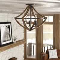 Traditional warmth meets industrial minimalism with this product. The rubbed black edges on the faux wood frame complements the rustic black finish of the inner rings. Curved arms and candelabra bulbs add classic charm to the chic simplicity of the drop silhouette.