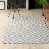 Set an artful foundation in your living room seating ensemble or give the master suite a makeover from underfoot with this essential area rug. Its bold geometric pattern makes it a perfect pick for modern spaces. Made in India, it's hand-tufted using wool with a low pile height that's easy to maintain with regular vacuuming.