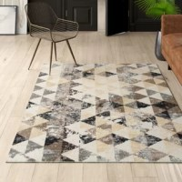 Set a contemporary foundation for your stylish space with this ivory area rug, showcasing a geometric triangle repeat. Machine made in India, this area rug is power loomed of stain- and fade-resistant polypropylene in a medium 0.4
