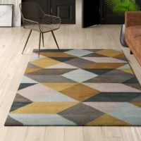 Featuring a modern geometric motif in gold, teal, blue, and light gray hues, this dynamic area rug brings a bit of mid-century inspiration into any arrangement in your home. Hand-tufted from 100% wool with a 0.75