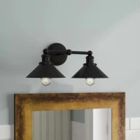 Brighten up your bathroom in classic industrial style with this two-light vanity light. Crated of metal in a blackened bronze finish, this fixture features a round backplate complete with molded edges and decorative screw caps, while a horizontal arm suspends two milled pendant holders. Peeking out from under a pair of cone shades, two 40 W ST58 Edison bulbs (included) disperse ambient light throughout your space to round out the design.