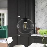 Bring a boost of brightness and a taste of what's trending to any arrangement in your home with this modern 1-Light Single Globe Pendant. Crafted from metal in a versatile solid finish, this fixture features a round canopy, an adjustable hanging cord, and a glass globe shade. The open bottom of the shade makes it easy to swap out compatible 40 W medium-base bulbs (not included). The manufacturer backs this product with a year warranty.