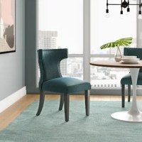 Transform your dining decor with the broadly designed Upholstered Dining Chair. Sweeping lines complement a minimalist shape for a chic look studded with nailhead trim. This Upholstered Dining Chair comes generously padded with dense foam covered, non-marking foot caps and delivers just the right touch of finesse with tapered wood legs. Sporting an hourglass shape, this Upholstered Dining Chair works well in a variety of dining room arrangements.