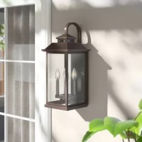 This takes cues from traditional outdoor lighting but adds a more modern shape. Clear glass sides softly diffuse the illumination of the lamp. A curved hook seemingly keeps the fixture in place. This traditional take on the lantern will add a warm and welcoming element to your home's exterior.