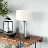 There's an endless amount of table lamps out there, but this simple and modern design is just what you need to finish out your room in style. It showcases a tapered body crafted from clear seeded glass, which reveals a center metal rod that finishes out the lamp with a square base down below. Up top, an off-white linen drum shade conceals a 60W bulb (not included) that brightens up your bedside or provides a bit of reading light in your living room.