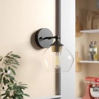 This mid-century modern sconce is just as stylish as it is functional. This 1-light wall sconce showcases an eye-catching glass shade, reminiscent of a wine glass. A matte black finish and gold accent socket enhance the look. The shade also pivots, so you can customize the illumination in your home. Plus, it's fully dimmable with a compatible dimmer switch (sold separately) so you can turn it down low for dinner. This wall sconce accommodates 60W bulbs: We recommend adding an Edison bulb for...