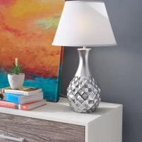 This chic table lamp, with its metallic silver painted ceramic body and white fabric shade, will add a dash of glamour to any space.