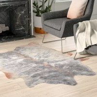 Set a sophisticated foundation for your stylish space with this gray faux cowhide area rug! Made in Brazil, this area rug is hand-tufted from 100% polyester faux cowhide in a low 0.25