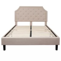 Anchor your bedroom in tasteful, transitional style with this upholstered platform bed. Founded on a solid wood frame, this bed features a crown arched headboard upholstered in neutral polyester fabric, while button tufts and nailhead trim lend a tailored touch. Clean-lined foot and side rails accommodate your preferred mattress without the need for a bulky box spring or bunky board, while four legs and a series of posts create under bed clearance for valuable storage space.