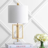 Love the geometric structure of this brass body paired with the marble-like base-a pairing that feels contemporary and luxurious. Featuring a silk-wrapped cord and a brass finial, this piece is stylish from head to toe. This lamp is perfectly scaled to sit atop a desk, armoire, or side table.
