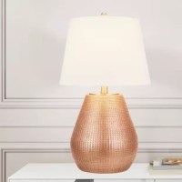 Illuminate your home in more ways than one with this table lamp. The gourd-shaped body of the lamp features finely chiseled detail carvings with an on-trend copper finish bringing the feeling of textures and layers to the design. Topped with a linen shade featuring a silken liner inside the shade leaving no detail behind. This piece is crafted with high-quality materials with copper metal accents and a 3-way rotary switch allowing you to choose the level of ambient light.