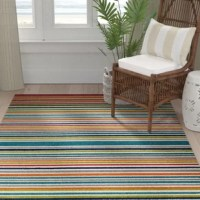 Stylish enough to live indoors with enough muscle to withstand the elements, this indoor/outdoor rug brings the best of both worlds to any space you call home. Dressed in multi-colored stripes, this design ups the energy of your decor. Made in the USA on state-of-the-art looms, it's woven from stain- and fade-resistant polypropylene yarn with a low pile that stands up to high foot traffic. To clean, vacuum regularly and spot treat spills. A rug pad is recommended.