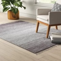 Handcrafted in India from 100% cotton, this modern area rug showcases gradient stripes that transition into a lighter center to create an ombre effect. Fringe accents adorn either end to offer up a touch of texture. Outfitted in neutral gray hues, this design is versatile enough to blend with a variety of color palettes and aesthetics. Wherever you decide to roll this rug out, we recommend you pair it with a rug pad to help it stay put.