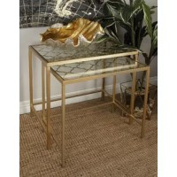 Stylish and dimensional metallic gold metal accent tables with metal quatrefoil patterns. These nesting tables are rectangular and crafted from solid iron, including the unique quatrefoil grid beneath each clear glass top. Nested together or separated, this set of gilded tables makes for lovely accent furniture or stylish side tables in your contemporary space.