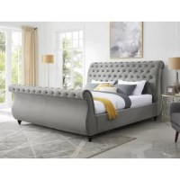 This bed features a sleigh design with a scrolled headboard and footboard. Nailhead trims line the sides of the rolled headrest and footrest and the side rails.