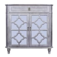 This corner cabinet has 1 drawer, 2 mirrors backed doors with quatrefoil carvings, antique-style hardware, and bun feet. Hand-painted in a multi-layered process which makes each piece unique and no 2 exactly alike.