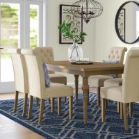 Add some traditional charm to your dining room or kitchen with this stylish seven-piece dining set. Its clean-lined table is crafted from solid wood in a neutral hue with visible wood grain and features four turned legs and a clean look. Its six chairs are upholstered in solidly-hued polyester fabric and accented with button tufting for an eye-catching look.