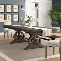 Anchor your dining room in French country style with this extendable dining table. Crafted from solid and veneer wood, this piece features a distressed dark ash finish and acacia veneers for a rustic look. The charming design showcases a smooth planked tabletop and an intricately-carved reverse scroll trestle base with a metal crossbar. Two removable leaves expand the table to comfortably accommodate up to ten, while tasteful millwork and moldings offer charismatic craftsmanship and traditional...