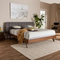 With its clean lines and low profile, this bed adds cool retro style to your bedroom. Inspired by mid-century modern design, this bed is built with a low platform set on top of angled legs. The warm walnut brown-finished wood frame is paired with a soft, chic fabric upholstered headboard that provides a comfortable spot to lean against. Its extended width and channel tufting add a sleek, modern feel. The bed is made in Malaysia and requires assembly.
