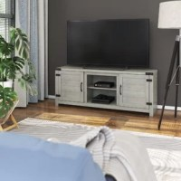 From binging your favorite show to checking out the latest headlines, TVs are a must-have item in our home. So give it the perfect perch with this rustic TV stand! Crafted from engineered wood, this piece boasts a streamlined silhouette with a natural hue that gives it traditional appeal. Two side cabinet doors with a plank design open up to reveal storage space with adjustable shelves to store games and blankets, while two middle shelves are perfect for other living room essentials. Cable...