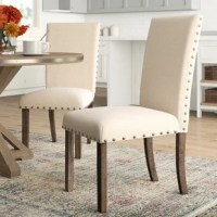 Lend your dining ensemble a touch of farmhouse-chic style with this traditional 40'' H x 20'' W x 26'' D side chair. Its inviting foam-filled seats are upholstered in charming beige linen and accented by metal nailhead trim for an eye-catching touch. Smokey walnut finished legs featuring distress marks give this chair a slightly weathered look and a cozy feel. Plus, it arrives in a set of two!