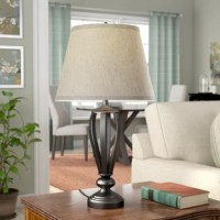 Looking to lighten up your space without sacrificing style? This statement-making table lamp is a piece of art all on its own. Sold as a pair, this set showcases an openwork middle that adds depth and dimension. It is crafted of metal in an oil-rubbed bronze finish, that adds traditional appeal. Let it top your living room end table to tie together a traditional seating group or add it to your nightstand to build a beautiful bedside vignette. A drum shade sits atop this base, concealing one...