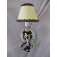 This sconce has a handmade monkey sitting atop green palm tree leaves and another monkey hanging from the arm.