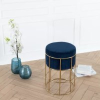 The Nordic design of this accent stool will change your mind. Inspired by the stylish simplicity of Scandinavian design, this collection exhibits modern minimalism with clean-lines and a plush round top. Upholstered in a luxurious velvet fabric adds sumptuous elegance that will add a glamorous and luxurious feel to a girly boudoir. By the means of artistic intervention, the gold powder coated base is hand welded into a minimalist cage-like shape. The golden finish gleams beautifully on catching...