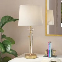 The Maye 29'' Table Lamp is dressed for a cocktail party with two stunning faceted crystals that create the main focus. Without a worry in the world, the crystals gleam with delight as the light, veiled by the white linen shade, shines, and the brushed brass finish adds luxe and simple opulence. With the electrical socket at the base allowing you to charge all of your devices, this table lamp is a wonderful lighting statement to any room in your home.