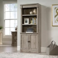 Put a pop of personality into any arrangement with this versatile bookcase, featuring three open shelves that let you show off framed photos, artful accents, your favorite novels, and any other items that make you smile. Two cabinet doors below open to reveal concealed storage space, so you can tuck odds and ends out of sight. Crafted in the USA from manufactured wood, this piece sports a wood grain finish that's neutral enough to blend with a variety of color palettes and aesthetics. Full...