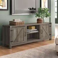 Bring a little barn-inspired style to the living room with this TV stand, accommodating a TV of up to 70''. Crafted from manufactured wood, this stand features rustic doors with wood grain patterns, exposed hardware, and a streamlined silhouette for the look of a modern farmhouse pick. A pair of adjustable open shelves give you spots to display DVD players and often-watched DVDs, while a pair of drawers lend even more space to stash your collection of entertainment accessories.
