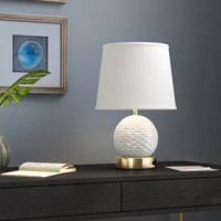 The Locke 18'' Table Lamp incorporates a whimsical and rotund design that is as playful as it is beautiful. Beautiful wavy ridges add depth to the white spherical body, highlighted even more by the soft illuminating light shining from within the linen shade. The base has an integrated electrical socket--perfect for charging all of your devices. Whether it shines in your living room or bedroom, this lamp will perfectly accentuate your home's beauty.