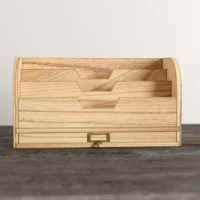 Crafted of wood in a rustic finish, this desktop organizer strikes a rectangular silhouette with curved sides and an open top. Showcasing a metal label frame and a built-in handle pull, one drawer offers out-of-sight storage for smaller accessories, while three portioned slats make it easy to sort folders, files, and mail. Measuring just 7