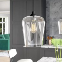 Modern and minimalist, this one-light bell pendant brings a touch of on-trend style as it shines a light down on any space. Crafted from metal, this fixture features a round sloped-ceiling-compatible canopy and a slender, adjustable downrod in a matte black finish that blends easily with a variety of color palettes and aesthetics. A tapered clear glass shade completes the look, providing a peek at a compatible 60 W medium-base bulb (not included) ensconced within.