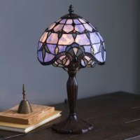 Highlighted by hand-cut pieces of stained glass, this Tiffany-style table lamp adds Art Nouveau elegance to your master suite or study. Complete the vignette with artfully patterned vases, endearing statuettes, and eye-catching candleholders.