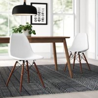 Bring a touch of modern design to your space in a cinch with this simply chic dining chair. Crafted from molded plastic in a matte colored finish, this chair features a bucket seat with a full backrest and a waterfall edge. Sporting a light, natural stain, four solid wood legs include plastic foot caps to save your floors from scuffs and scratches, while architectural stretchers lend added stability and support.