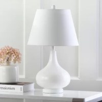 Illuminate your space in a chic, streamlined style with this table lamp! Crafted of glass in a glossy finish, this table lamp strikes a teardrop-shaped silhouette on a round pedestal base. Up top, a cotton empire shade fluorescent medium based bulb (60 W incandescent-equivalent, not included) to diffuse ambient light as it's dispersed throughout your space. Powered by a 59.6