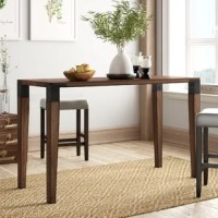 Introduce a warm and modern touch to your space with this Deskins Counter Pub Table. Simple in design, this wooden counter table features metal accents that complement the warm pecan finish of the legs and tabletop. Complete your industrial style décor by incorporating this counter table into your dining room or entryway.