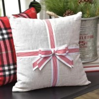 Create a cozy and welcoming retreat with this traditional pillow. This gorgeous product is constructed from premium linen. The pillow is accented with an oversized red and white stripe ribbon bow on the front. It's traditional colors and detailed accents make this a great accent piece to enjoy for years to come. Premium pillow insert included.